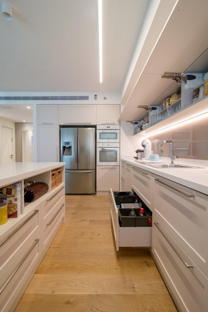 07 מגירה מתחת לכיור עם שני פחים ותכשירי נקיון וסדרת קלאפות כאחסון נח עם דלתות שאינן בתחום ההפרעה לראשו של אדם  העובד במטבח