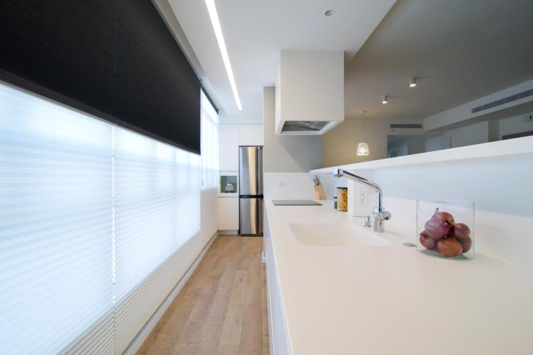 09 לאי המפריד בין הסלון למטבח גב המייצר נישה המאשפרת אחסון מוצרים לשימוש מטבחי המוסתרים לעין מהחלל הציבורי