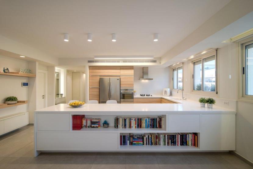 20 מטבח עם חצי אי הפונה לחלל המגורים והמשרת אותו כספרייה נמוכה. משטח העבודה הרחב נח לעבודות אפייה ומשרת גם 3 כסאות לארוחות קלות