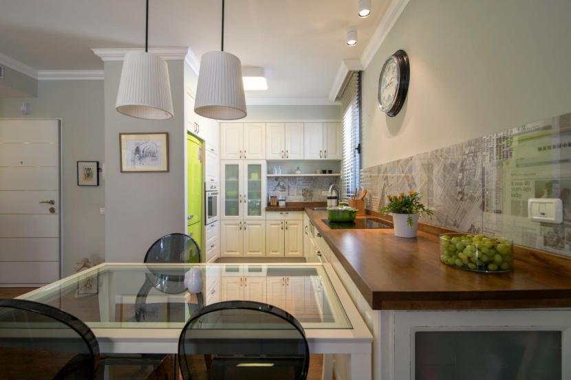26 מטבח בעיצוב מודרני כפרי עם משטח עבודה מעץ. ואזור פתוח המאפשר תצוגה ואחסון בפינת המטבח. חיפוי קיר באריחים מודפסים עד גובה 60 סמ.