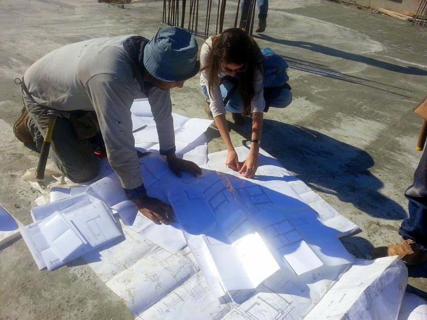 3 מליסה עוברת עם עמר על התכניות על הבטון שזה עתה התקשה 3