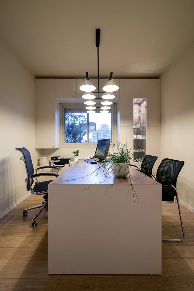 שולחן עבודה עם תאורה תלויה הממקדת את האור על השולחן עצמו