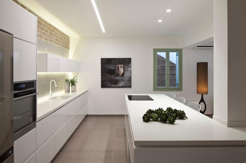 התמונה על הקיר בקצה המטבח מושכת את המבט לקיר האחורי ומעצימה את הפרספקטיבה והתאם את תחושת העומק